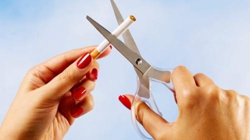 Девушка ножницами режет сигарету