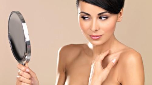 Красивая девушка осматривает лицо после выведения бородавок