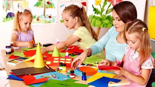 Девочки в детском садике с вопитателем делают поделки