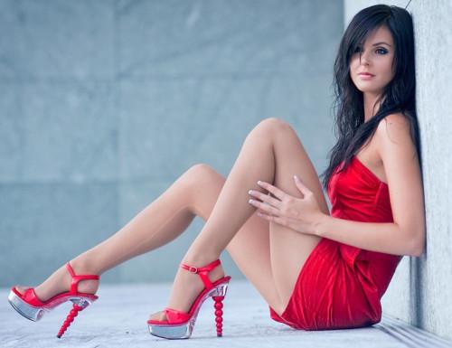 Девушка в красном платье сидит на полу