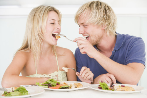 Парень и девушка кормят друг друга диетическими продуктами