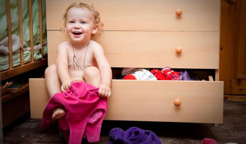 Маленький ребёнок одевает одежду