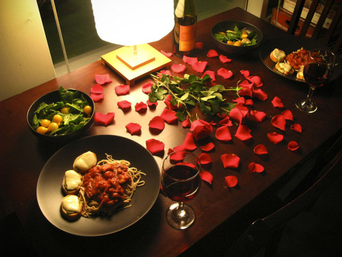 Красиво оформленный стол с едой и лепестками роз для домашнего романтического вечера