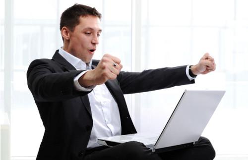 Мужчина сидит в позе лотоса за ноутбуком и читает статью - как быть успешным в жизни