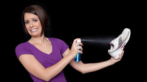 Девушка брызгает дезодорантом на обувь от которой исходит сильный запах пота