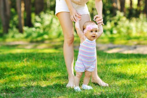 Молодая мама учит ребёнка делать первые шаги