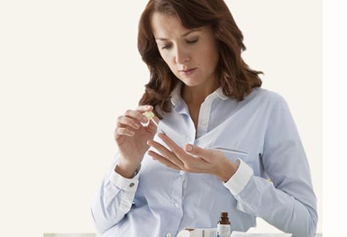 Женщина обрабатывает лекарством папиллому на пальце