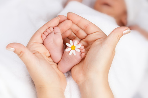Ножки новорожденного в руках мамы