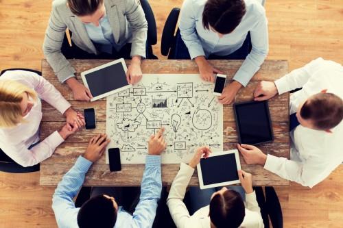 Сотрудники компании сидят в офисе за столом и думают над презентацией