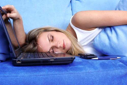 Девушка спит на диване, а рядом лежит ноутбук