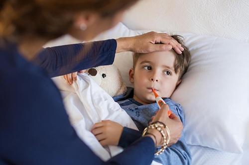 Женщина измеряет температуру у ребенка