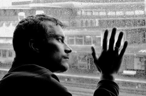Мужчина в плохом настроении сидит у окна и депрессирует