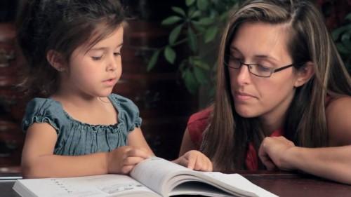 Женщина учит ребенка читать