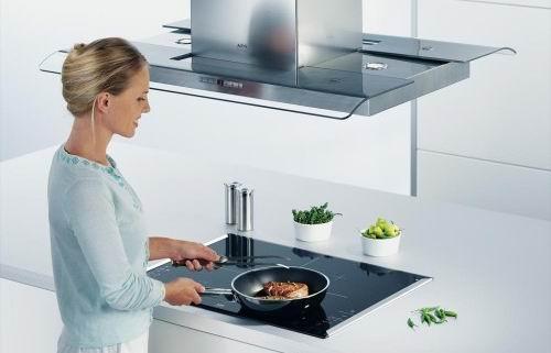 Женщина на современной кухне оборудованной вытяжкой готовит еду