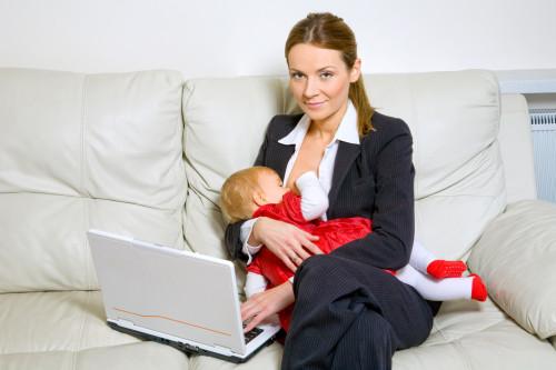 Мама за ноутбуком с маленьким ребёнком на руках, которого кормит грудью
