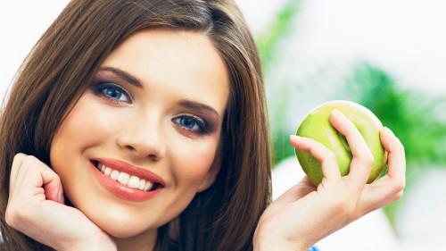 Красивая девушка улыбается и держит в руках яблоко