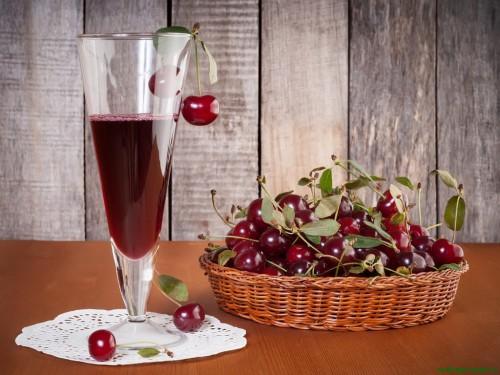 Вино из варенья и вишня лежат на столе