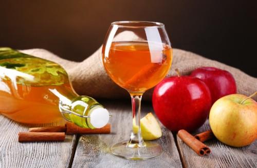 Яблоки и фужер с вином лежат на столе