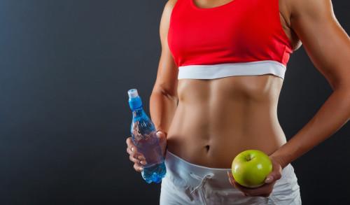Девушка со стройной фигурой держит в руке яблоко и бутылку с водой