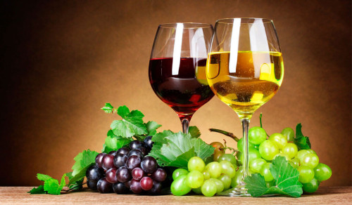Красное и белое вино вместе с виноградом лежат на столе