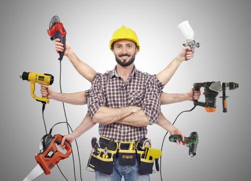 Мужчина строитель держит в руках строительные инструменты