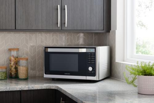Микроволновка серого цвета стоит на кухне квартиры