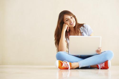 Девушка с ноутбуком в руках сидит на полу