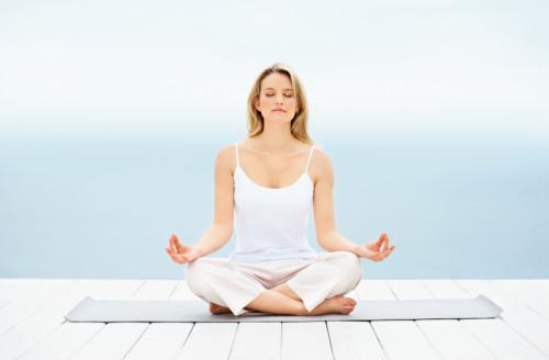 Девушка медитирует сидя на коврике