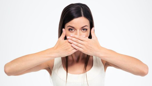 Девушка руками прикрывает нос
