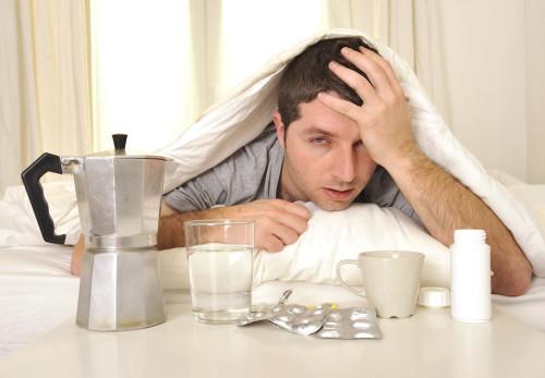 Мужчина, который отравился алкоголем лежит в постели и страдает