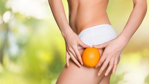 Девушка держит у бедра апельсин