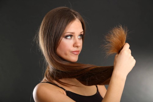 Девушка смотрит на свои секущиеся волосы
