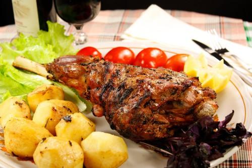 Баранья нога запечённая в духовке с овощами и листьями салата