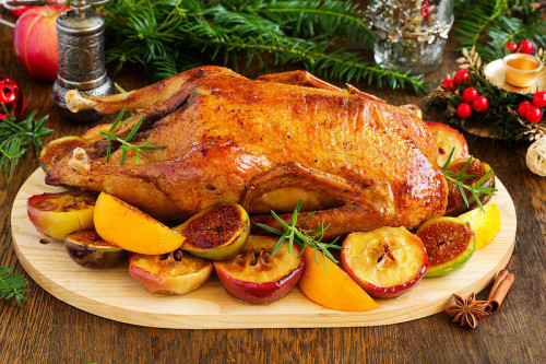 Утка с яблоками запечённая в духовке лежит на праздничном столе