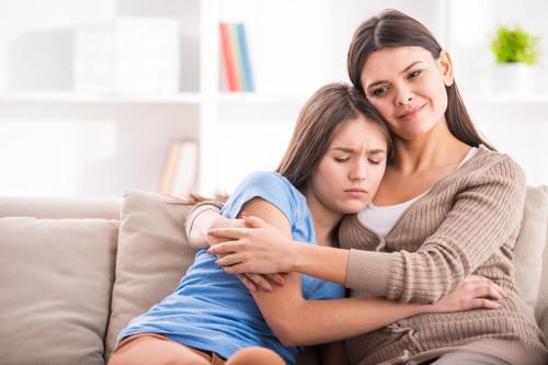 Мама и дочь сидят в обнимку на диване