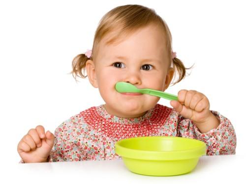Маленькая девочка ест ложкой кашу