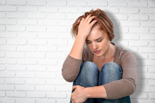 Девушка в депрессии сидит на полу и держится за голову