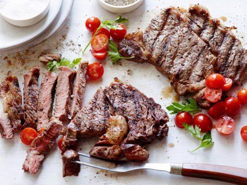Стейк из говядины приготовленный на сковороде лежит на столе с помидорами